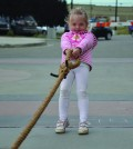 While her brother sits in the fire truck, Lilly Fogarty, 3, tests her strength by trying to pull the truck all by herself.