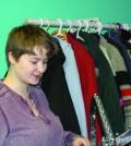 Phallon  Stoutenburg hangs clothing on the racks at the poverty outreach store. Photo: Julia Lovett
